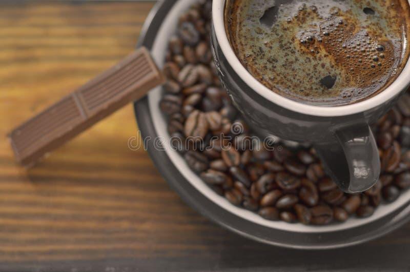 Tazza di caffè di Brown su un piattino con i chicchi di caffè fotografia stock