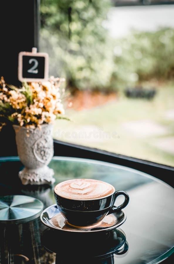 Tazza di caffè calda in caffetteria immagine stock
