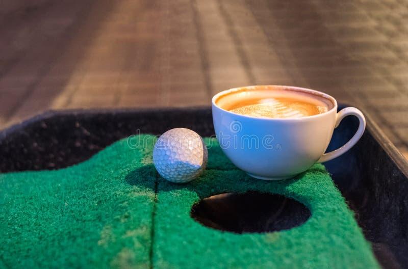 Tazza di caffè calda del latte con palla da golf su verde mettente fotografia stock