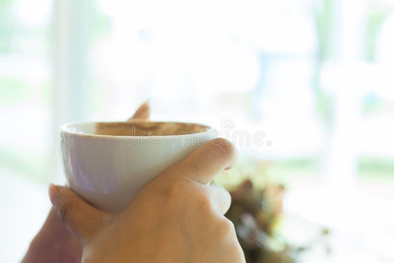 Tazza di caffè calda della tenuta femminile della mano fotografie stock