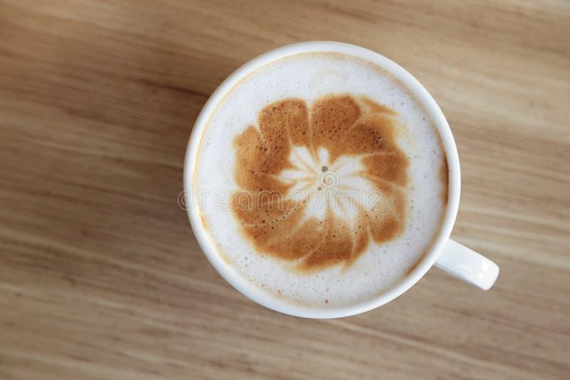Tazza di caffè caldo con arte del latte su fondo di legno fotografia stock