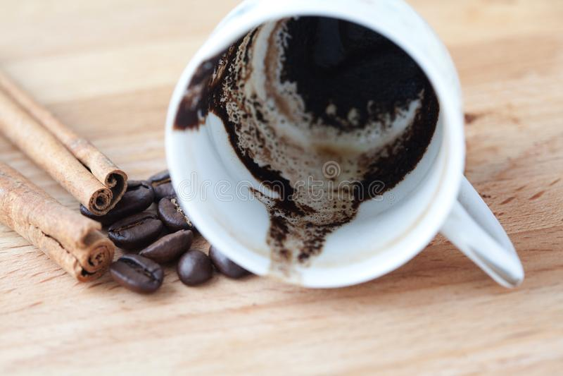 Tazza di caffè capovolta Motivi e fagioli di caffè fuoco molle, fondo di legno fotografie stock libere da diritti