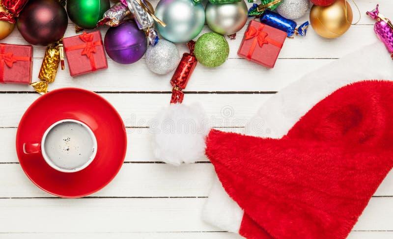 Tazza di caffè, cappello del Babbo Natale e bello decoratio di natale fotografia stock libera da diritti