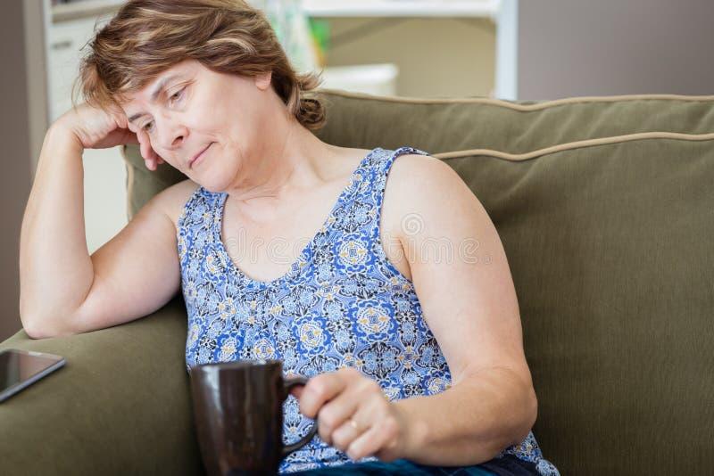 Tazza di caffè caucasica triste e depressa della tenuta della donna fotografia stock libera da diritti