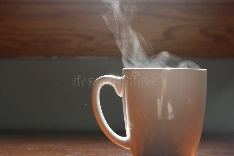 Tazza di caffè che cuoce a vapore alla luce solare sulla vecchia superficie di legno fotografia stock libera da diritti