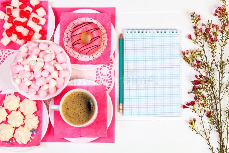 Tazza di caffè, ciambella, spuntini saporiti, taccuino, matita e fiori fotografia stock libera da diritti