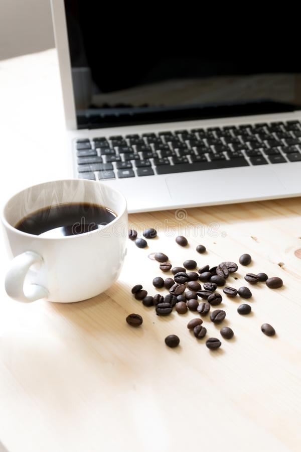 Tazza di caffè, computer portatile e chicchi di caffè spanti fotografia stock libera da diritti