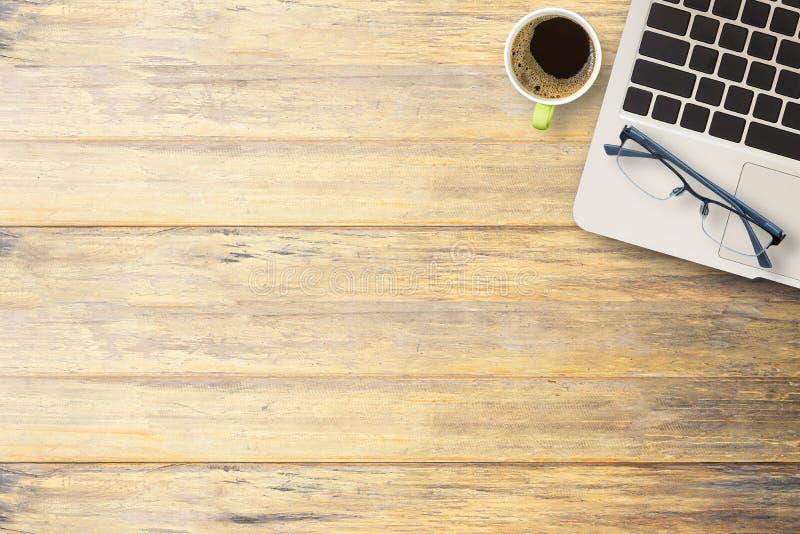 Tazza di caffè, computer portatile e vetri su una scrivania o su un wo fotografia stock