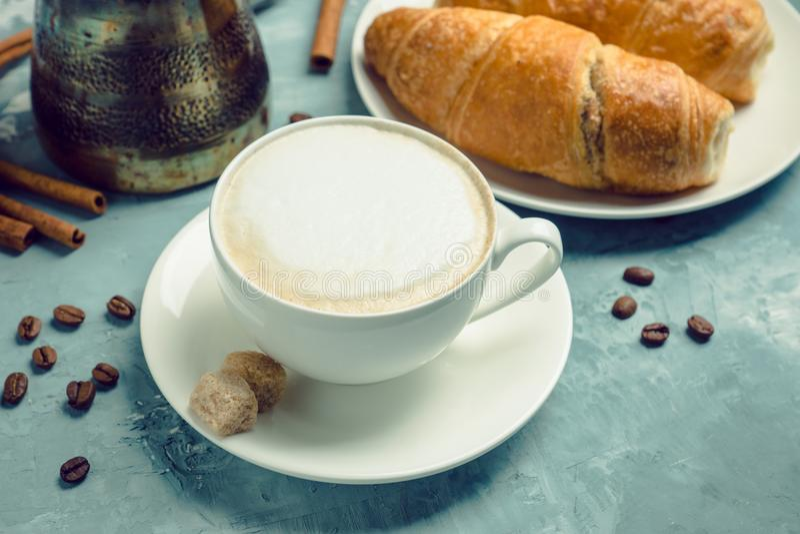 Tazza di caffè con i croissant sui precedenti di legno rustici fotografia stock libera da diritti