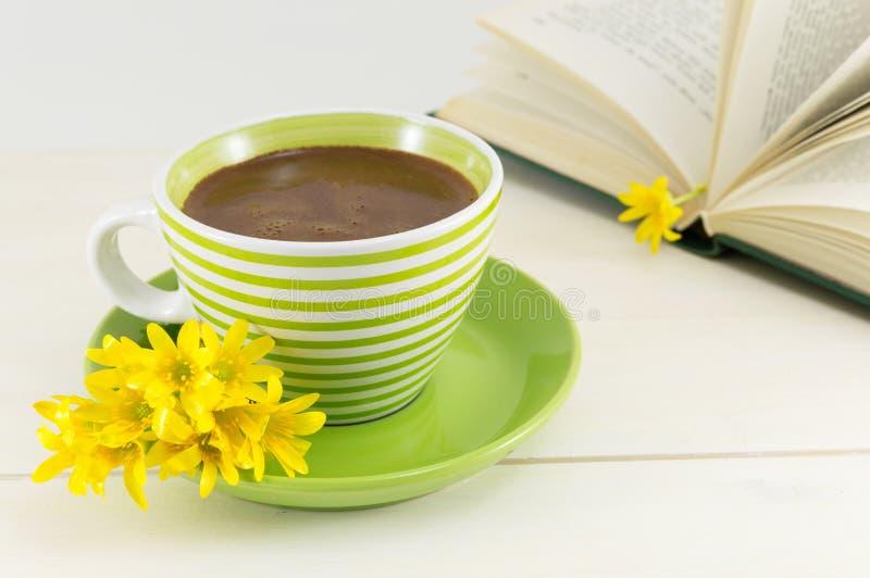 Tazza di caffè con i fiori freschi e un libro fotografia stock libera da diritti