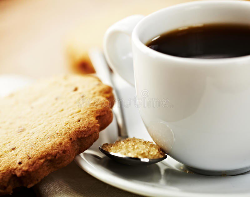 Tazza di caffè con il biscotto e lo zucchero marrone fotografia stock