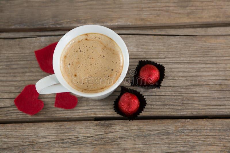 Tazza di caffè con il cioccolato ed i petali di rosa rossa immagini stock