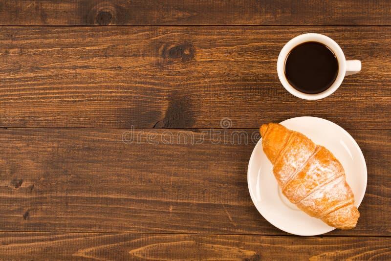 Tazza di caffè con il croissant per la prima colazione su una tavola di legno scura, vista superiore fotografia stock