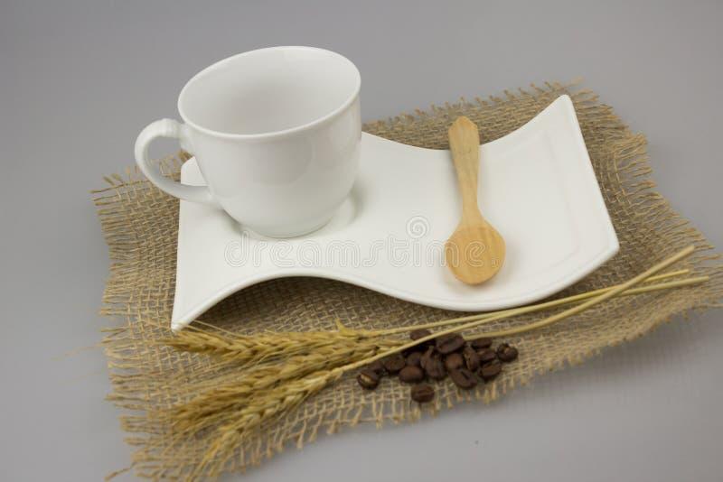Tazza di caffè con il cucchiaino sul tessuto dell'iuta immagine stock libera da diritti