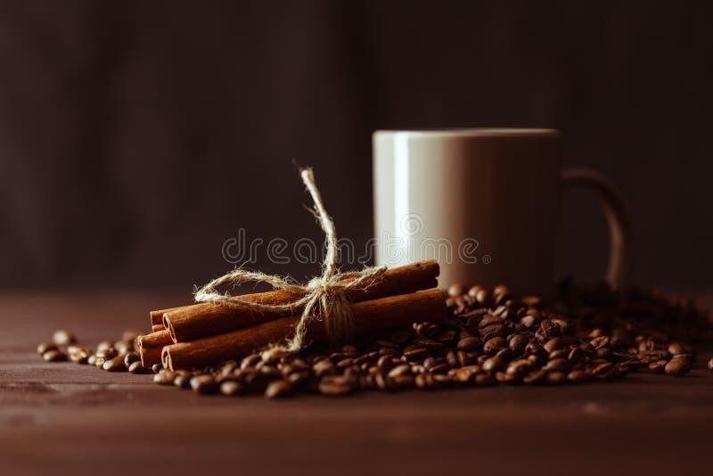 Tazza di caffè con il sacco della tela da imballaggio dei semi di cacao torrefatti sulla tavola rustica fotografia stock