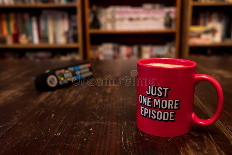Tazza di caffè con l'iscrizione appena un nuovi episodio e regolatore della ripresa esterna della TV fotografia stock