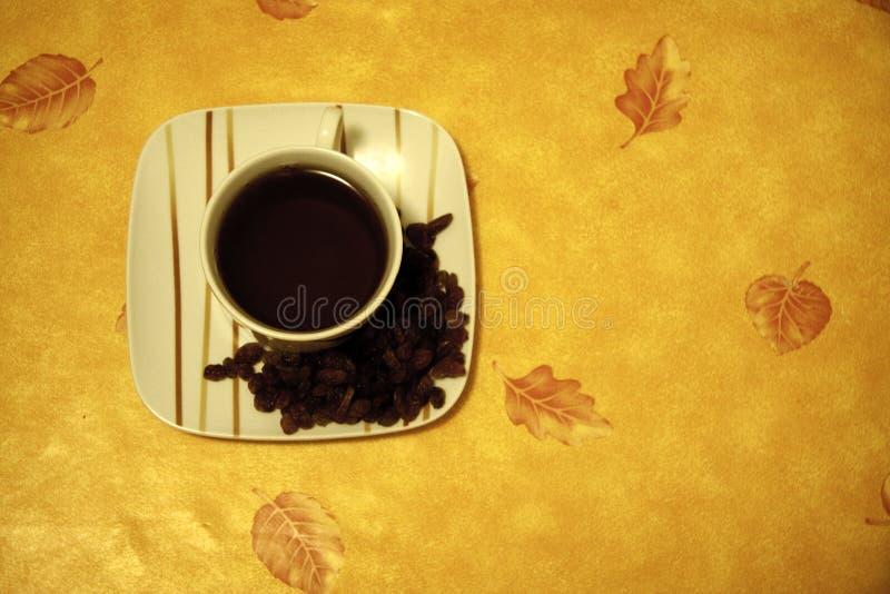 Tazza di caffè con l'uva passa fotografia stock