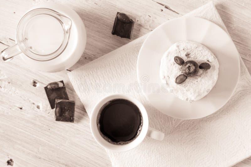 Tazza di caffè con la brocca di dolce e di cioccolato del latte sulla vista bianca del piano d'appoggio immagini stock libere da diritti