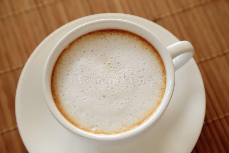 Tazza di caffè con la schiuma del latte sulla tavola di legno veduta dalla cima fotografie stock