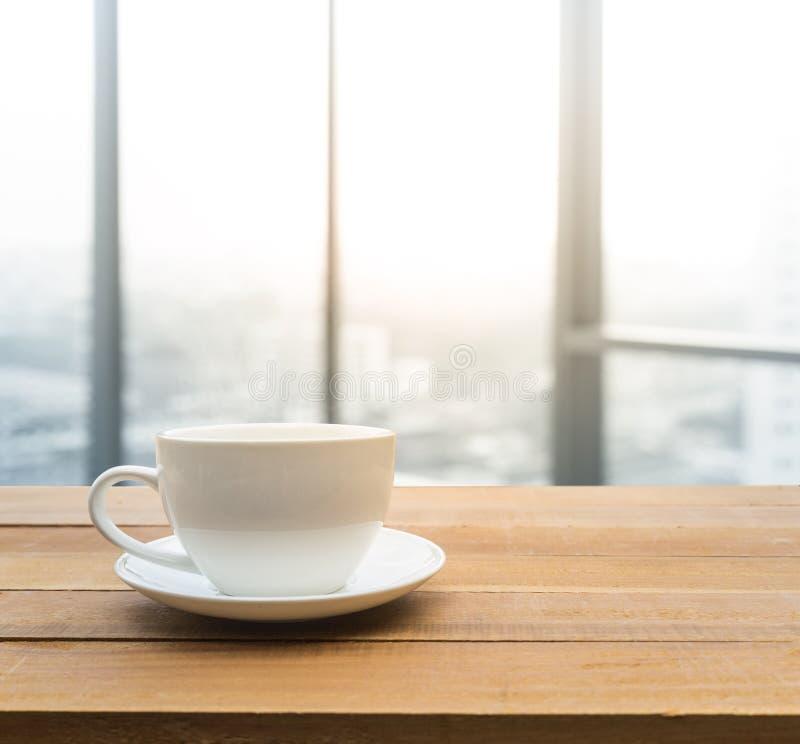 Tazza di caffè con la vista della città della finestra di mattina immagine stock