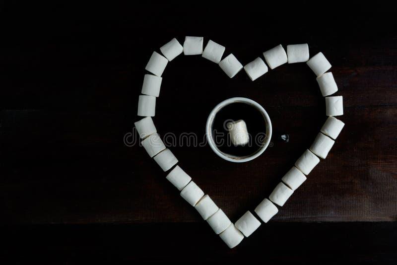 Tazza di caffè con le caramelle gommosa e molle fra le caramelle gommosa e molle nella forma della h fotografia stock libera da diritti