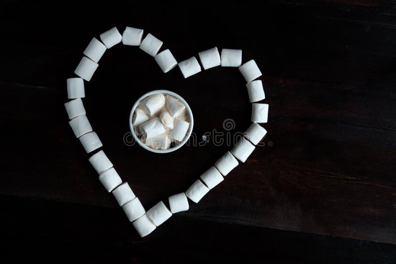 Tazza di caffè con le caramelle gommosa e molle fra le caramelle gommosa e molle nella forma della h immagine stock