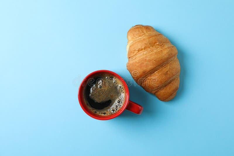 Tazza di caffè con schiuma ed il croissant schiumosi sul fondo di colore, spazio per testo e vista superiore immagini stock