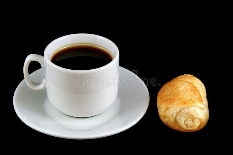 Tazza di caffè con un croissant isolato su un fondo nero immagini stock