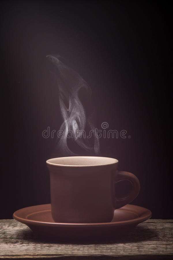 Tazza di caffè con vapore sul bordo di legno Priorità bassa nera immagine stock