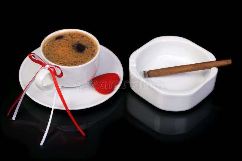 Tazza di caffè decorata con un arco e un cuore. Sigaro e portacenere su un fondo nero immagine stock libera da diritti