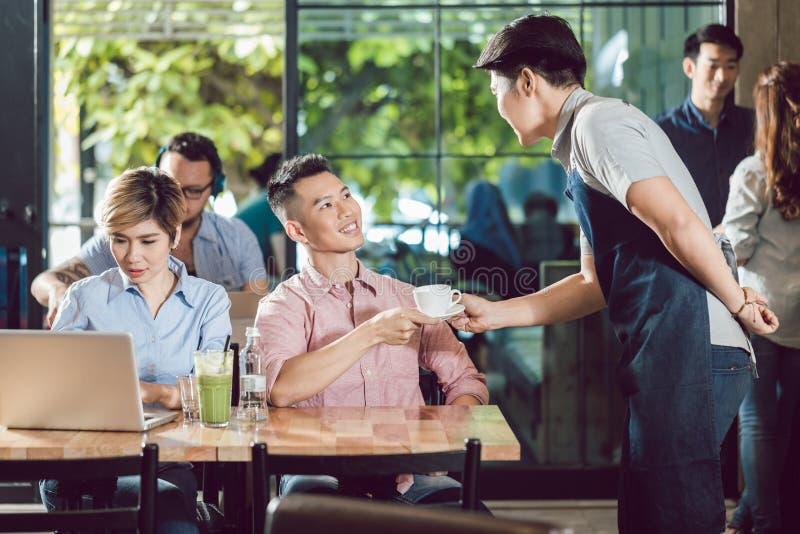 Tazza di caffè del servizio del cameriere al cliente fotografia stock
