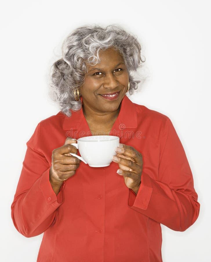 Tazza di caffè della holding della donna. immagine stock
