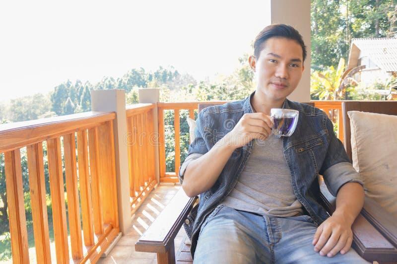 Tazza di caffè della tenuta del giovane o tè caldo fotografia stock