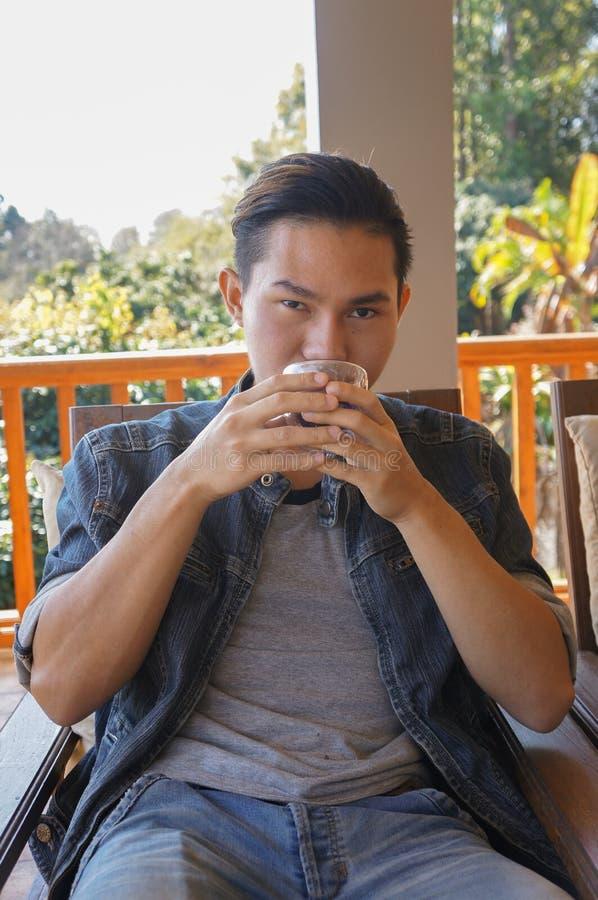 Tazza di caffè della tenuta del giovane o tè caldo fotografia stock libera da diritti