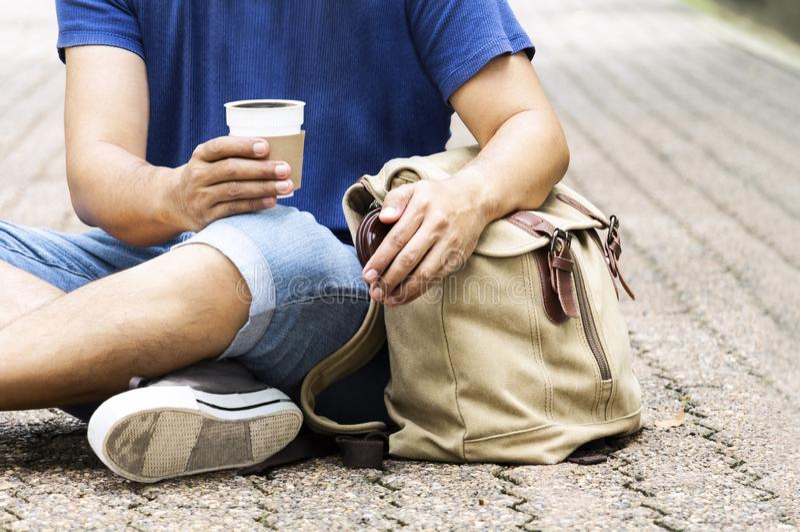 Tazza di caffè della tenuta dell'uomo della gente o tazza eliminabile con un pla nero fotografia stock