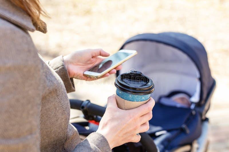Tazza di caffè della tenuta della donna da andare per mezzo dello smartphone durante la passeggiata con carrozzina Giovane donna  immagini stock