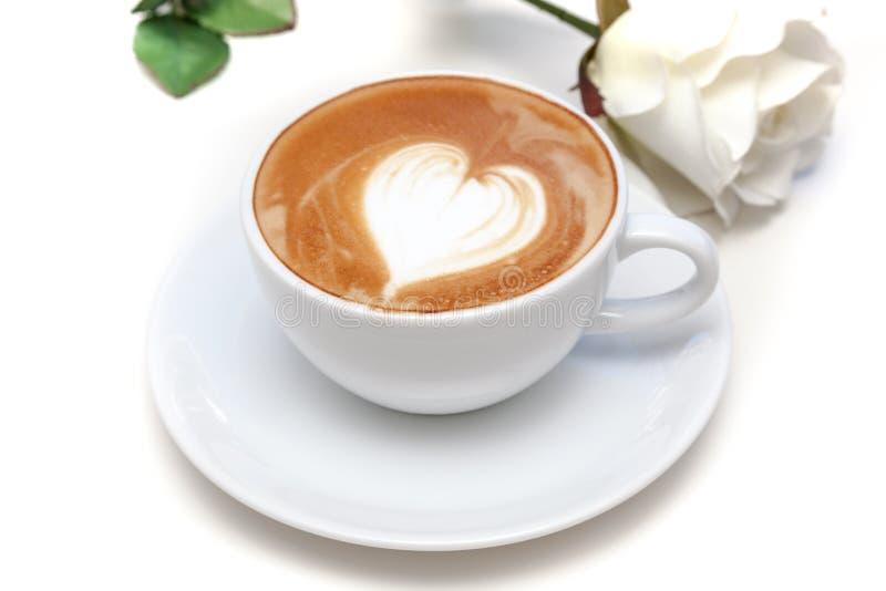 Tazza di caffè di arte del latte di forma del cuore sul piatto con la rosa di bianco fotografia stock