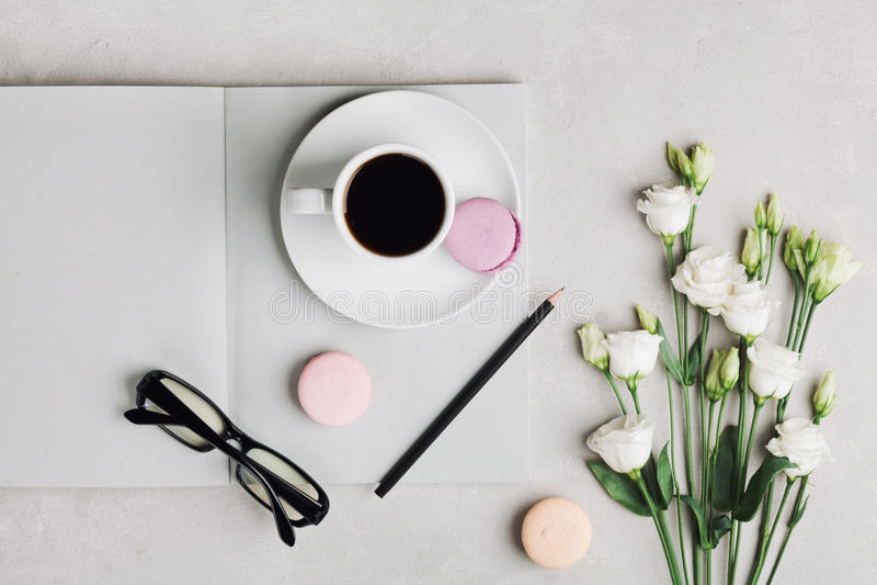 Tazza di caffè di mattina, taccuino vuoto, matita, vetri, fiori bianchi e macaron del dolce sulla vista leggera del piano d'appog immagine stock libera da diritti