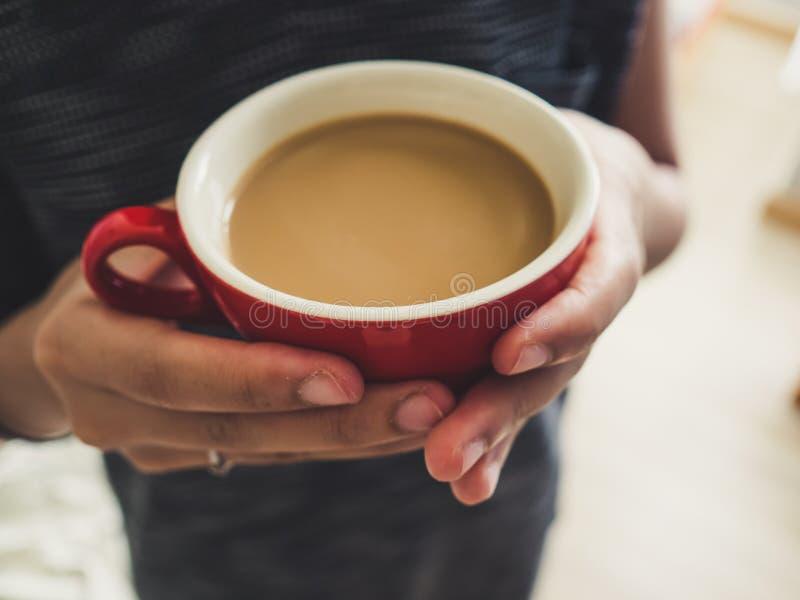 Tazza di caffè di rosso della tenuta della donna immagini stock