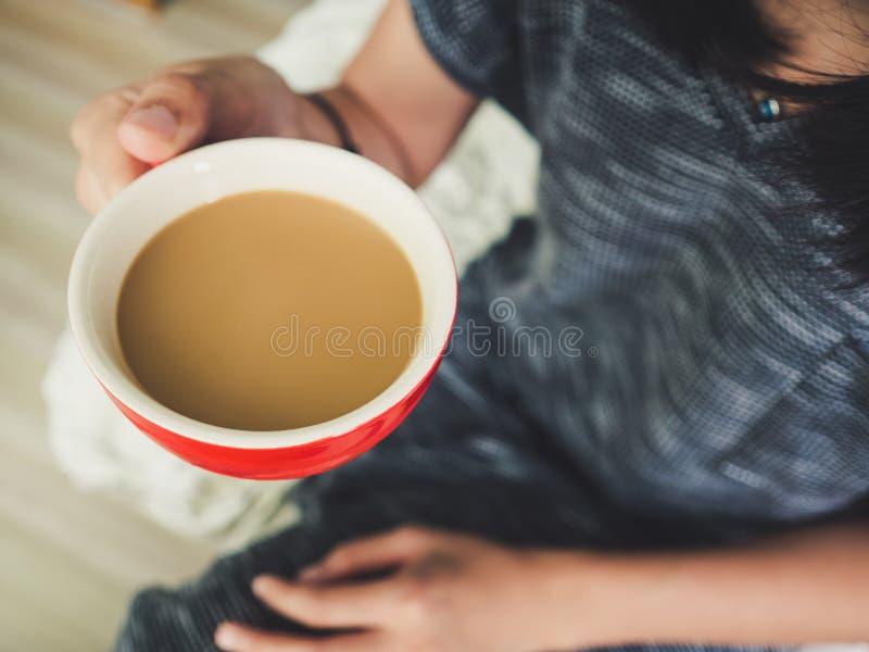 Tazza di caffè di rosso della tenuta della donna fotografia stock libera da diritti