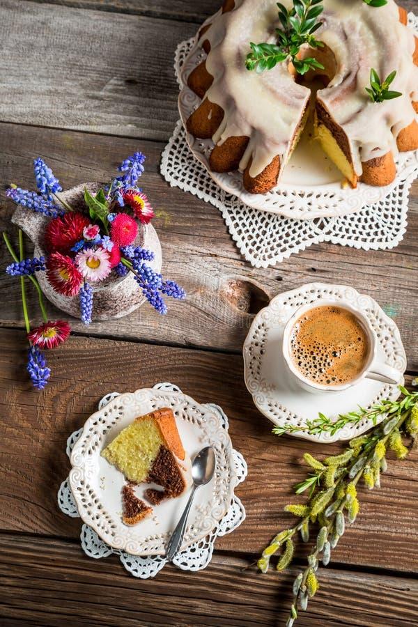 Tazza di caffè, dolce di pasqua e fiori della molla immagine stock