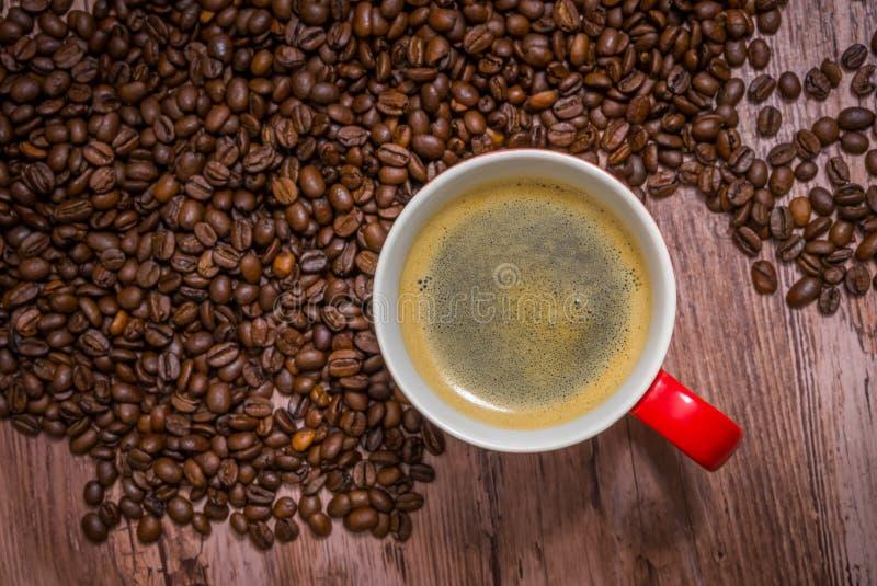 Tazza di caffè e chicchi di caffè rovesciati fotografia stock