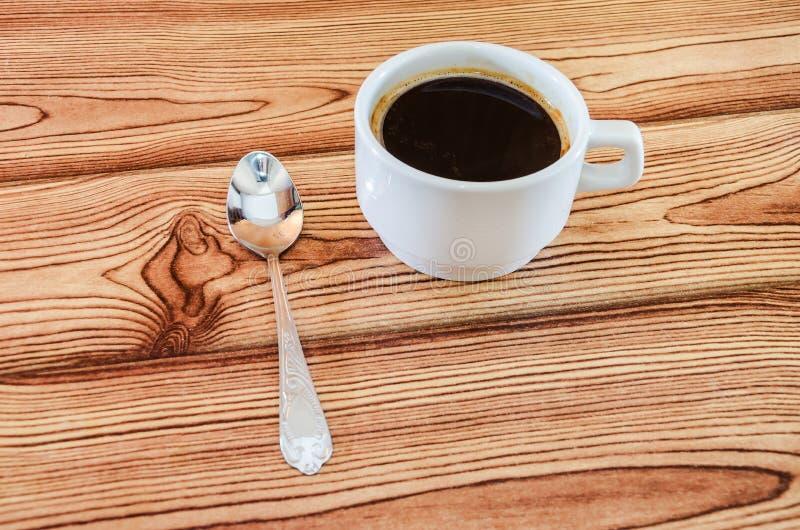 Tazza di caffè e cucchiaio su fondo di legno fotografia stock libera da diritti