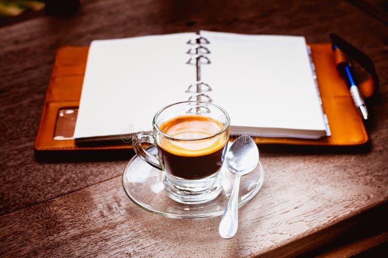 Tazza di caffè e del taccuino su vecchio di legno fotografie stock libere da diritti