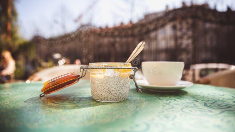 Tazza di caffè e dessert con i semi di chia in un barattolo di vetro su una tavola in un caffè fuori fotografie stock