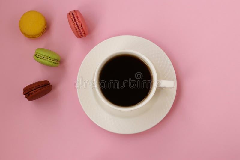Tazza di caffè e maccheroni francesi variopinti su fondo rosa, vista superiore, foto orizzontale immagini stock libere da diritti
