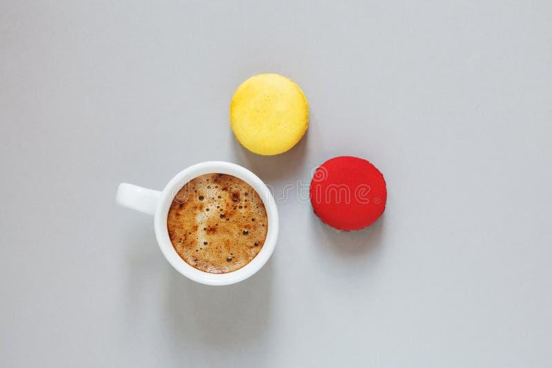 Tazza di caffè e paia dei macarons variopinti o dei maccheroni su fondo grigio, vista superiore fotografia stock