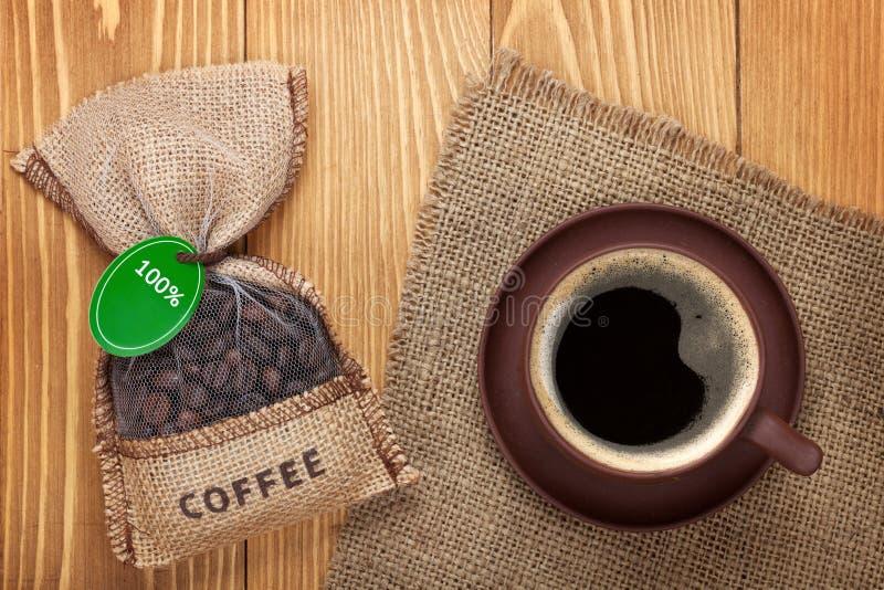 Tazza di caffè e piccola borsa con i fagioli fotografia stock libera da diritti