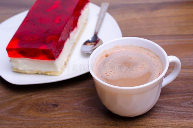 Tazza di caffè e un dolce sulla tavola in caffè fotografia stock