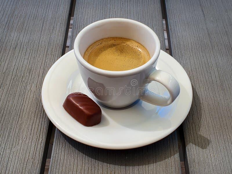 Tazza di caffè espresso con la piccola pralina del cioccolato sulla tavola grigia rustica fotografie stock libere da diritti